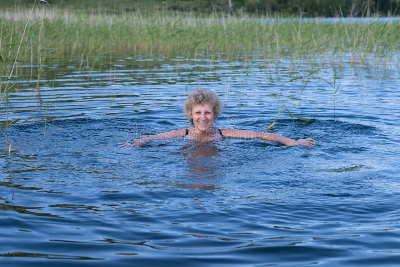Joyful elderly woman is swimming in the blue lake. stock image