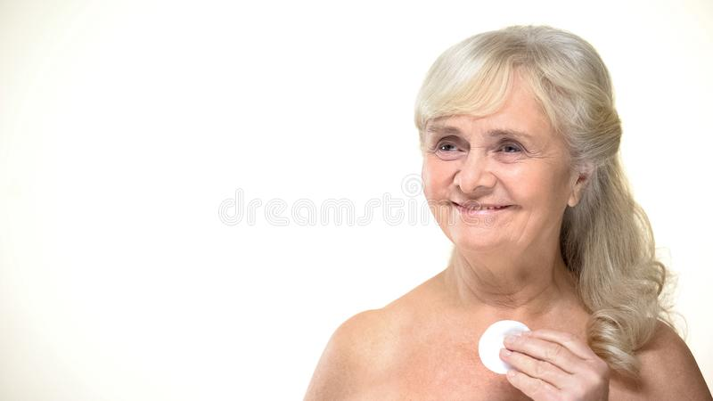 Joyful elderly woman using pad for skin cleansing, beauty procedures, cosmetics royalty free stock photo