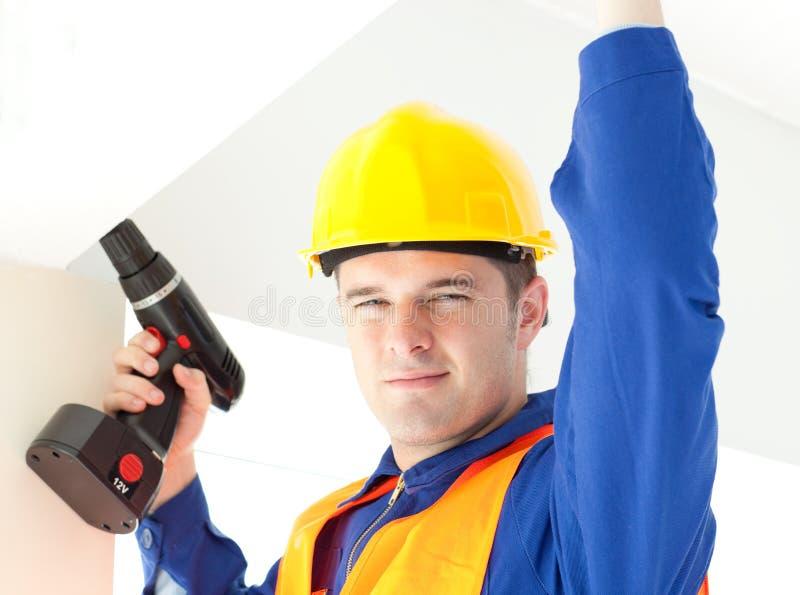 Joyful electrician repairing a power plan stock image