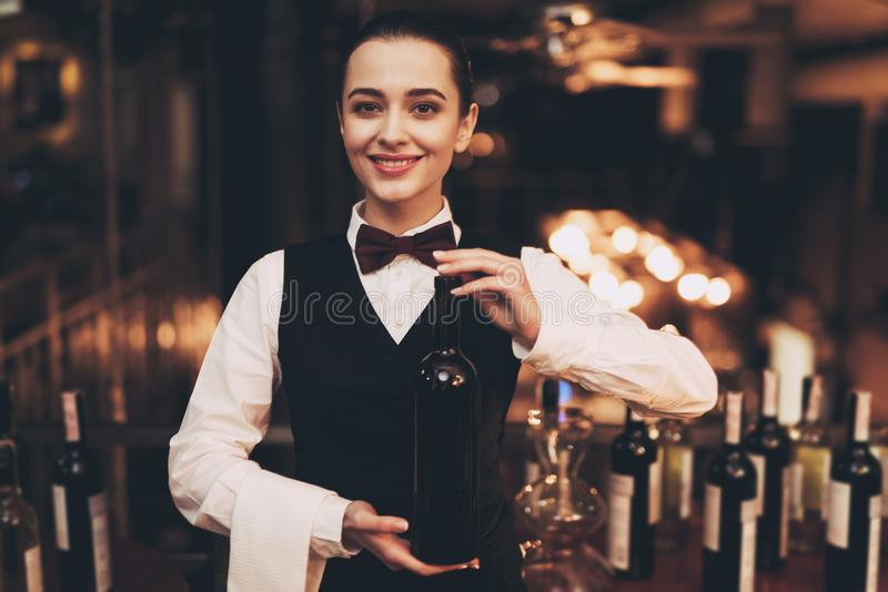 Joyful elegant waitress holding bottle of red wine, standing near bar. royalty free stock images