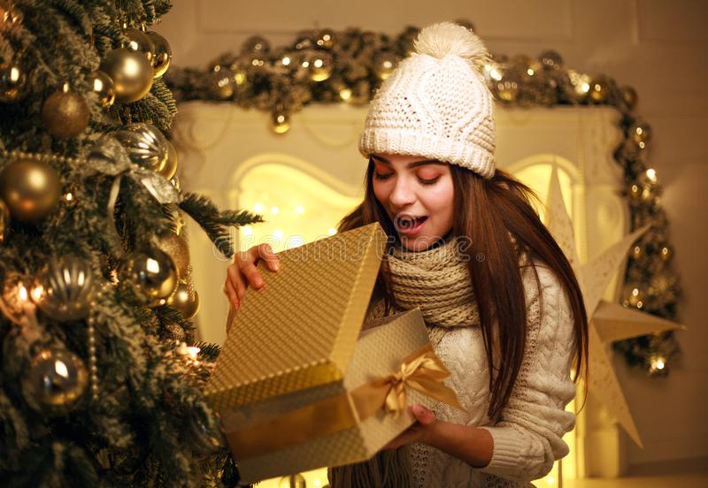 Excited girl opens Christmas gift at home in New Year`s decor. Joyful excited girl opens Christmas gift at home in New Year`s decor royalty free stock image