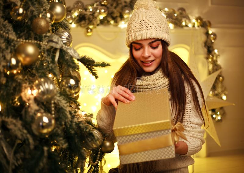 Excited girl opens Christmas gift at home in New Year`s decor. Joyful excited girl opens Christmas gift at home in New Year`s decor royalty free stock photography