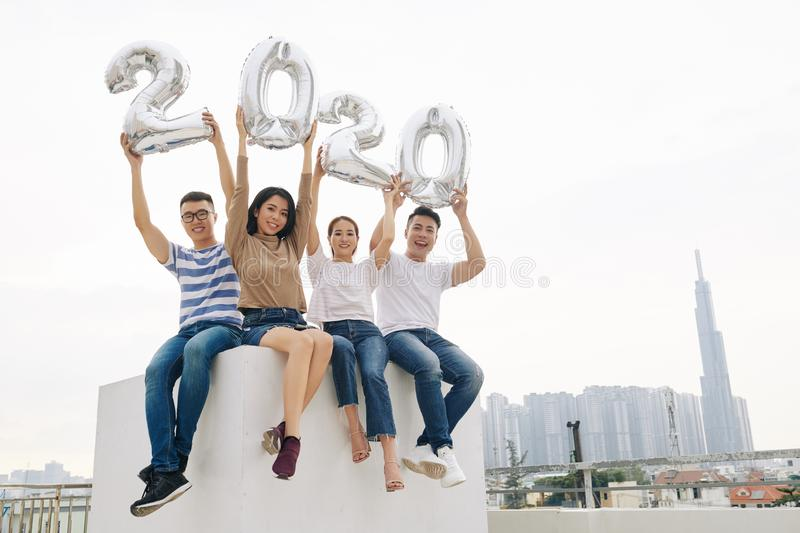 Excited young people showing balloon figures stock photo