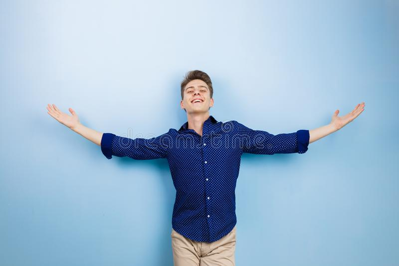 Joyful excited young dark-haired guy looking at camera with happy expression and raising arms, standing over blue royalty free stock photos