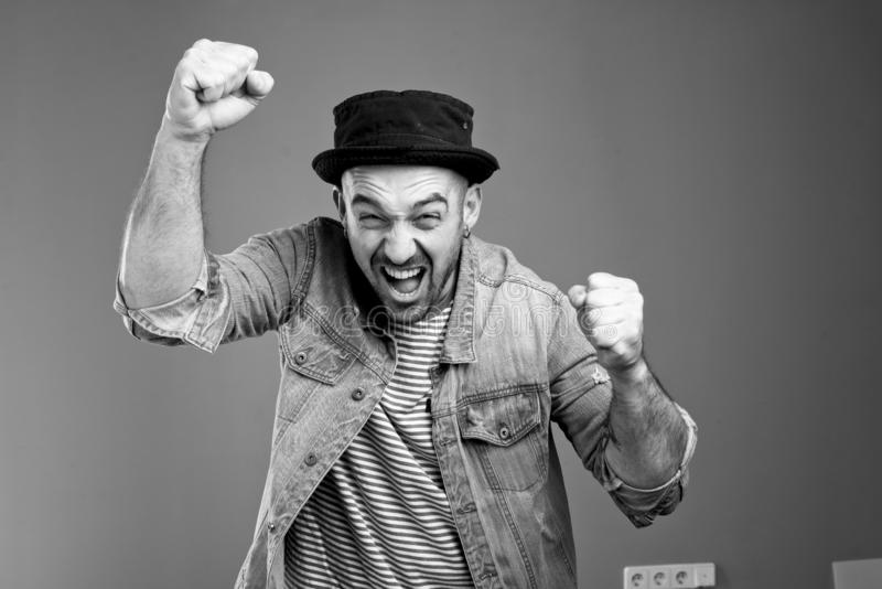 Joyful expressive man shouting at the top of his voice while raising his fists upwards stock image