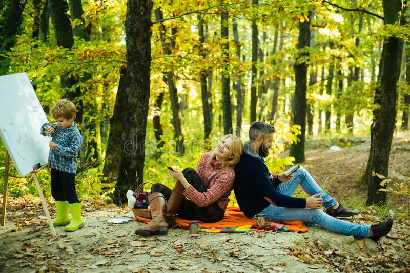 Joyful familie picnic. Handsome 4-years old son drawing family giving joyful moments to mom and dad. Parents using stock photography