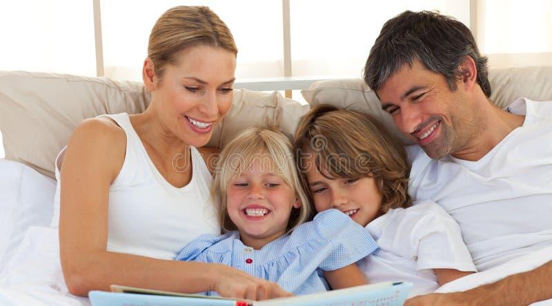 Joyful familj som läser en bok på underlag royaltyfri bild