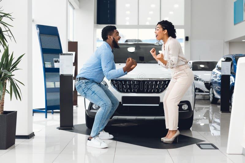 Joyful Family Couple Celebrating Buying New Car In Automobile Dealership stock photos