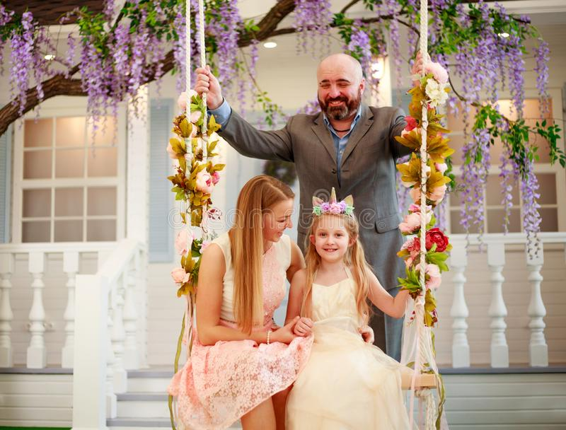 Joyful family parents with daughter at home in blooming garden on swing royalty free stock images