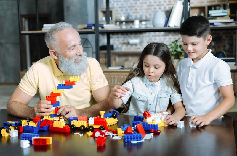 Joyful family playing with building block at home. Colorful leisure activity. Waist up shot of a positive minded elderly men and his grandchildren sitting at a royalty free stock image