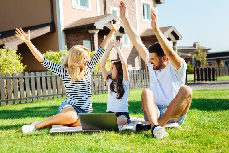 Joyful family raising hands while sitting on picnic royalty free stock images