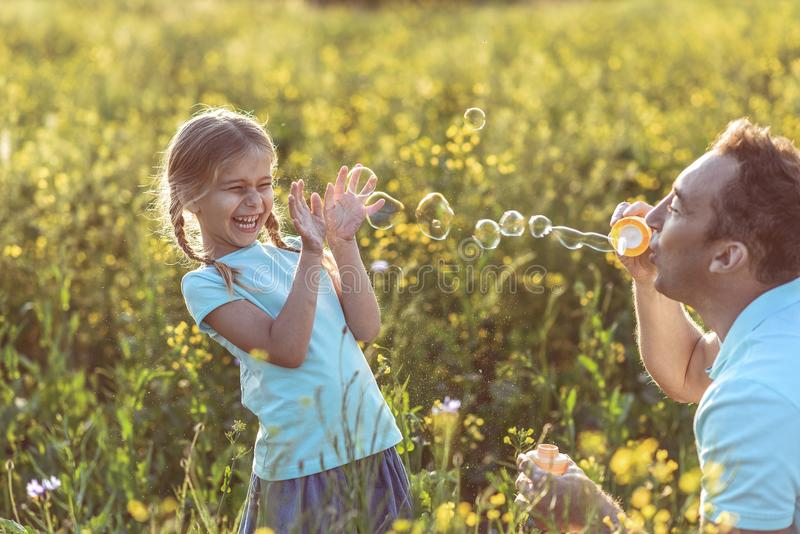 Cheerful girl having fun with dad on grassland royalty free stock photos