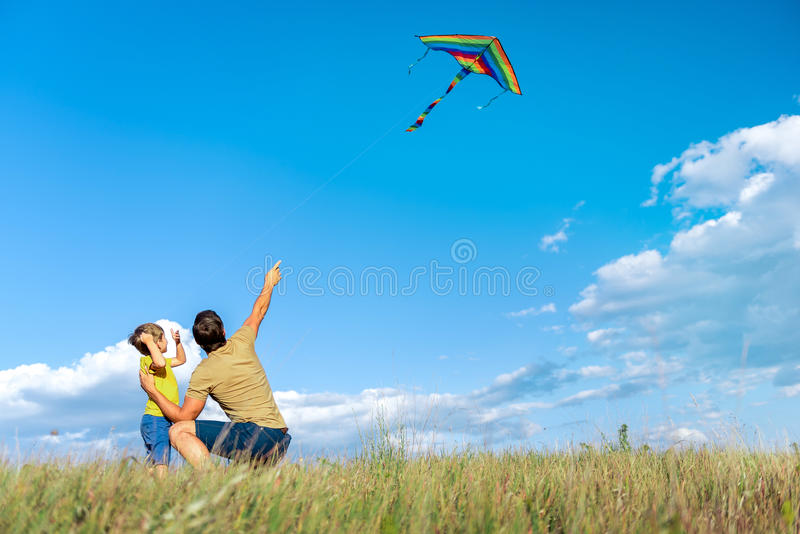 Joyful father and child playing together on grassland royalty free stock photography