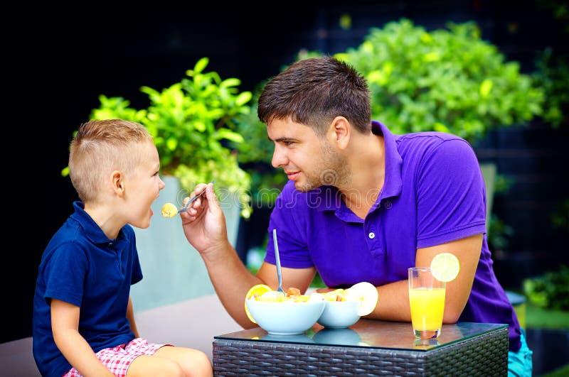 Joyful father feeding son with tasty fruit salad royalty free stock images