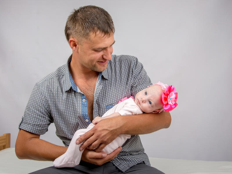 Joyful father holding newborn daughter and looks at her. Young dad sitting on a bed and holds her two-month baby daughter royalty free stock image