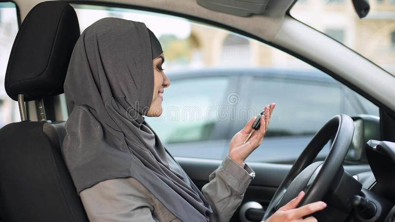 Joyful female in hijab holding car keys, new auto purchase, driving license stock image
