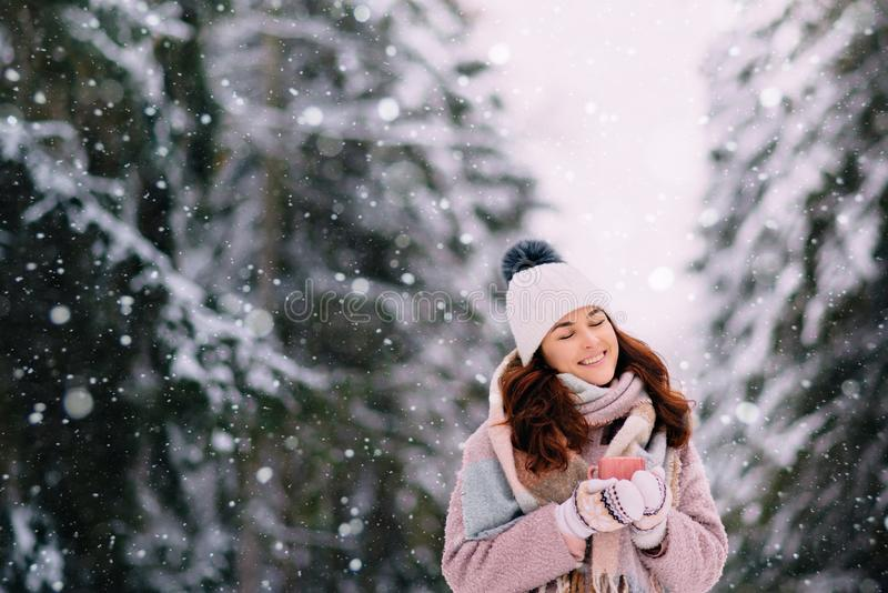 Joyful female stands in snowy park with cup of coffee in hands. Young woman holding cup of tea in her hands and standing in snow-covered park royalty free stock images