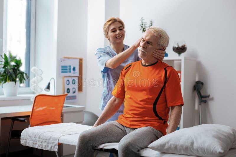 Joyful friendly female nurse massaging patients head royalty free stock image