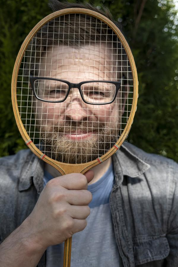 A joyful, funny man put glasses on a badminton racket and leaned against his face for a joke. Close-up royalty free stock photos