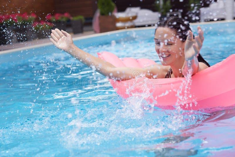 Joyful funny model splashing water in swimming pool, swimming with mattress, raising her hands, having fun in water, enjoying her. Rest at spa resort, chilling royalty free stock image
