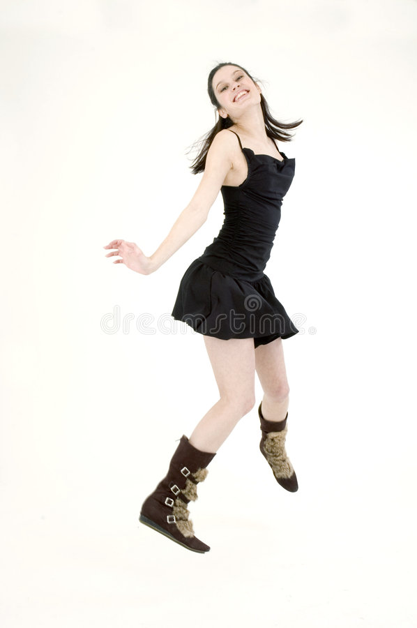 Joyful girl. Young dancer, in black short skirt and trendy fur boots, jumping on a white studio background stock image
