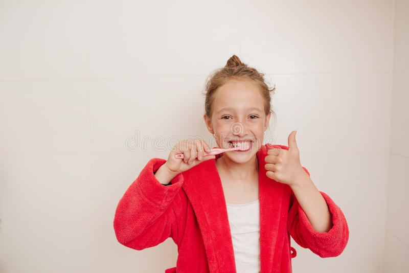 The joyful girl brushes teeth in a bathroom royalty free stock photos