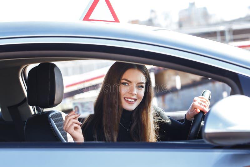 Joyful girl die een trainingsauto bestuurt met een rijbewijs in haar handen royalty-vrije stock foto