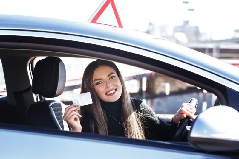 Joyful girl die een trainingsauto bestuurt met een rijbewijs in haar handen royalty-vrije stock afbeeldingen