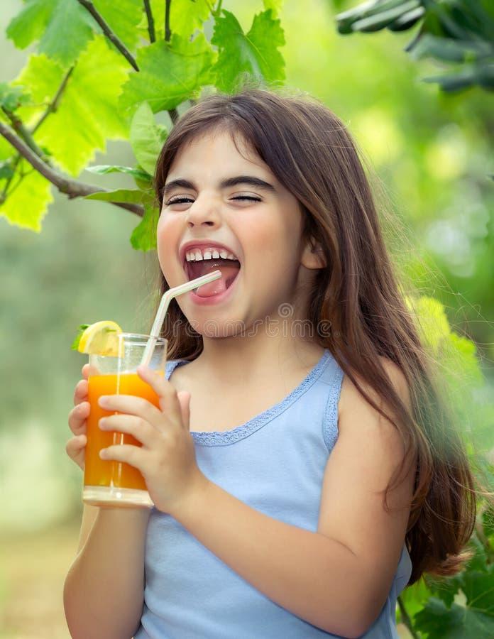 Joyful girl drinking juice stock photos