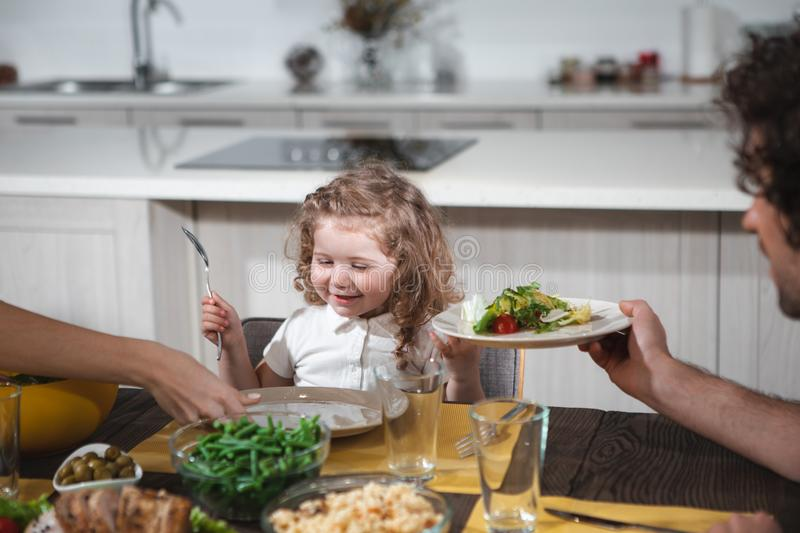 Joyful girl eating salad together with parents stock images