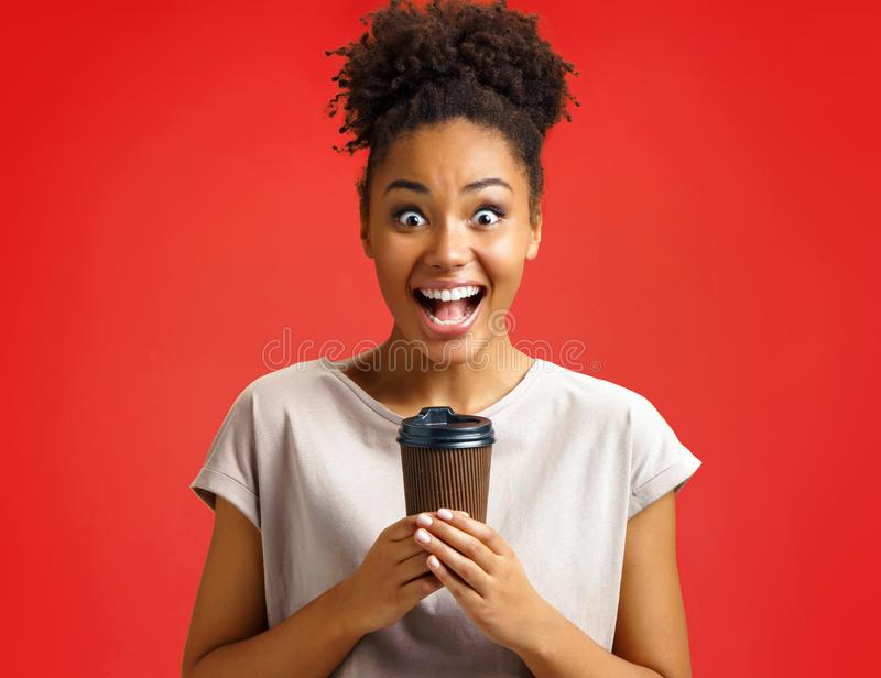 Joyful girl holds cup of hot coffee. stock images