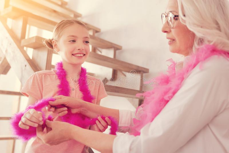 Joyful girl playing with feather boa at grandmas house stock images
