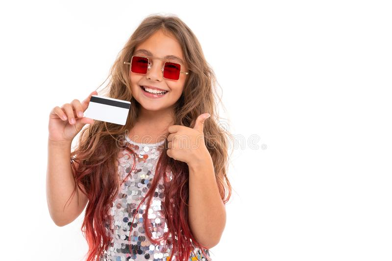Cheerful girl in square red sunglasses holding plastic bank card and giving thumbs-up gesture solated royalty free stock images
