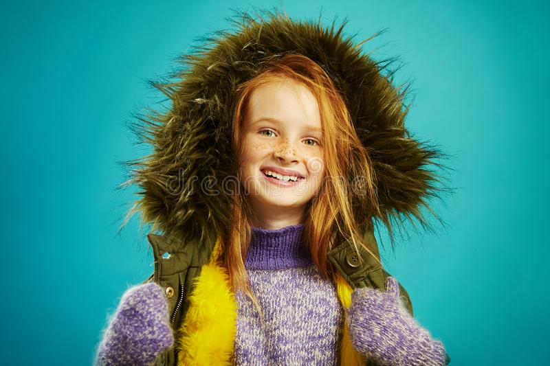 Joyful girl of ten years in winter clothes over blue background. Red haired child with beautiful freckles smiles. Dressed in warm jacket, fur hood, sweater stock images