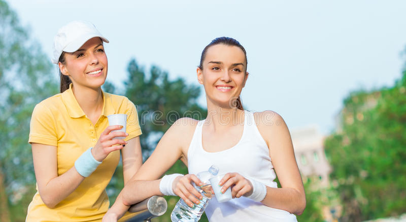 Download Joyful Girlfriends In Sports Clothing Drinking Water Stock Image -  Image of entjoyment, health