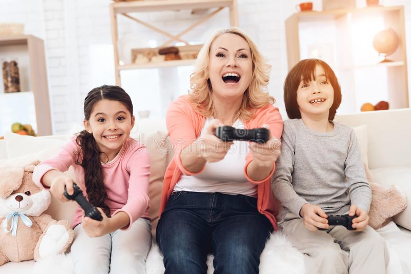 Joyful grandmother with cheerful grandchildren playing on game console sitting on couch. royalty free stock images