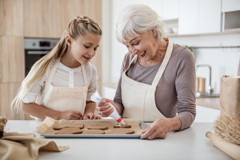 Cheerful girl baking holiday sweet food with granny stock photos