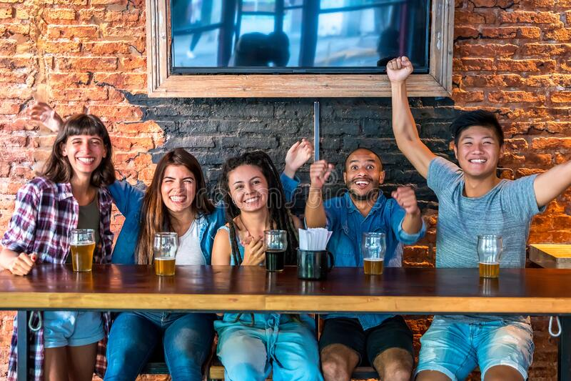 A joyful group of friends together in a bar royalty free stock photography