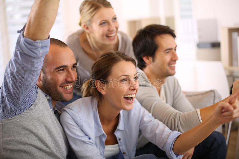 Joyful group of friends watching football game. Cheerful group of friends watching football game on tv royalty free stock image