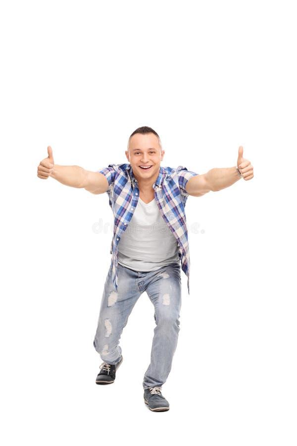 Joyful guy with an attitude, giving thumbs up. Full length portrait of a joyful guy with an attitude, giving thumbs up, smiling and looking at the camera stock photos