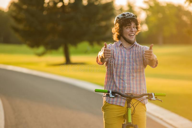 Joyful guy on bike gesturing thumbs up. Handsome young cyclist showing two thumbs up outdoors. Summer activity and sport royalty free stock photo
