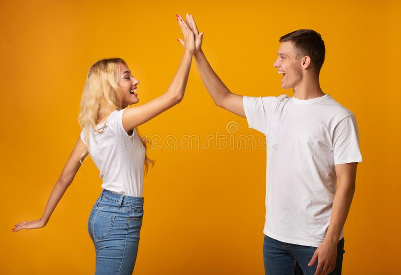 Joyful Guy And Girl Greeting Each Other With High Five. Joyful Millennial Guy And Girl Greeting Each Other With High Five, Clapping Hands Over Yellow Background stock photo