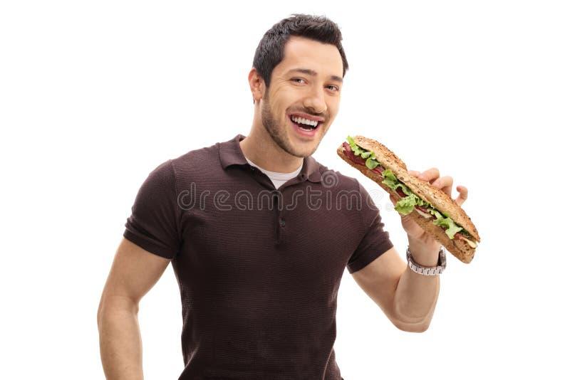 Joyful guy having a sandwich. On white background royalty free stock image