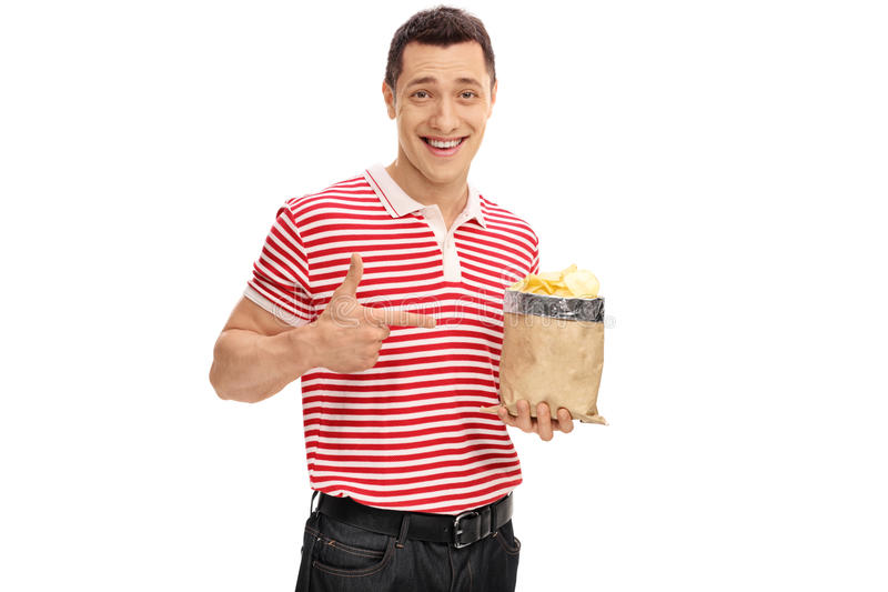 Joyful guy holding a bag of chips. And pointing at it isolated on white background stock image