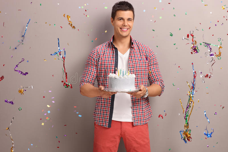 Joyful guy holding a birthday cake. With confetti streamers flying around him stock photos