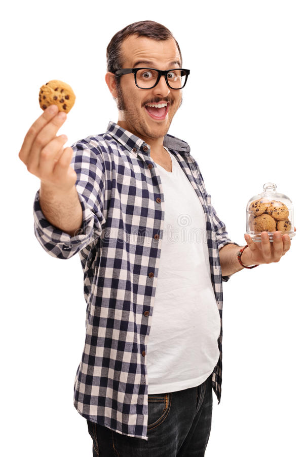 Joyful guy holding a jar of cookies. Vertical shot of a joyful guy holding a jar of cookies in one hand and a single cookie in the other isolated on white royalty free stock images