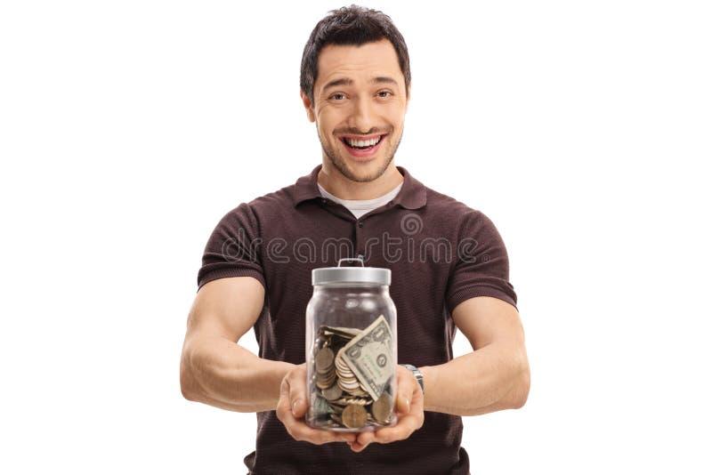 Joyful guy holding a jar full of money. Isolated on white background royalty free stock photo