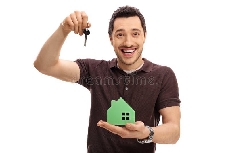 Joyful guy holding a key and a model house. Isolated on white background royalty free stock image