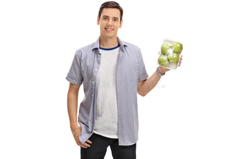 Joyful guy holding a pack of apples. Isolated on white background stock photo