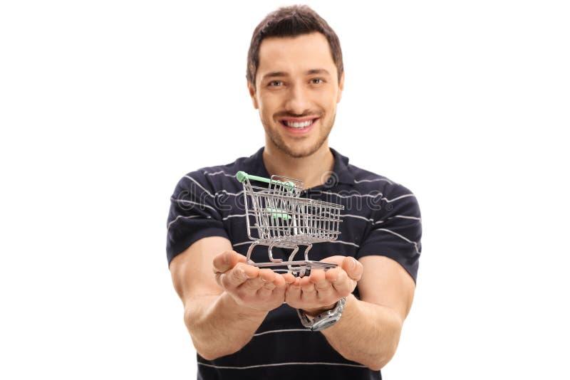 Joyful guy holding a small empty shopping cart. Isolated on white background royalty free stock image